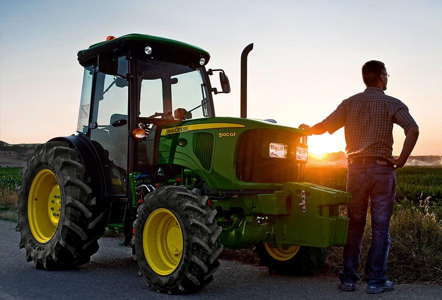 Used Equipment - man standing by John Deere tractor