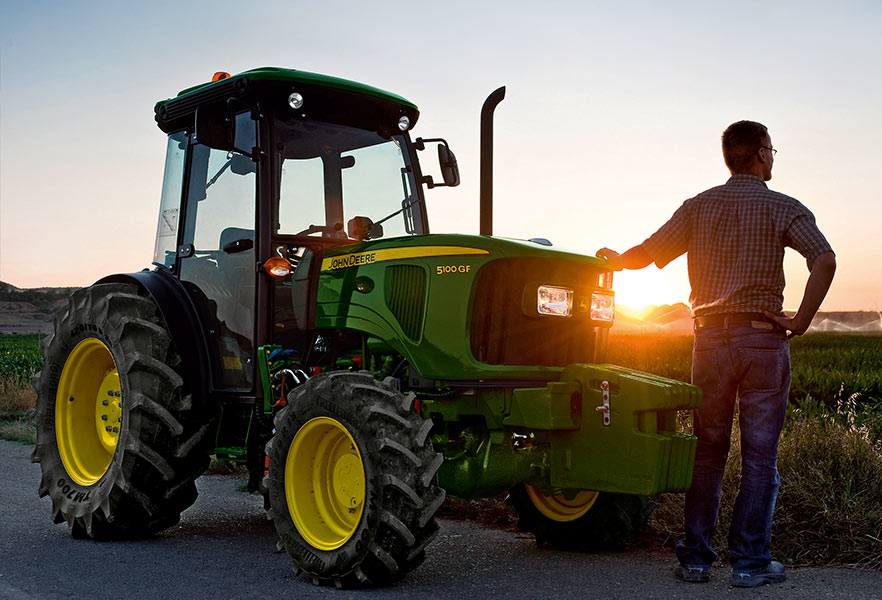 Used Equipment - man standing by John Deere tractor