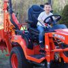 Happy kid atop a Kubota Compact Tractor