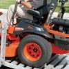 Man driving Kubota Z725 onto a trailer. Source: kubotausa.com